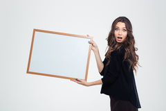 Chica joven atractiva que muestra al tablero en blanco Imagen de archivo