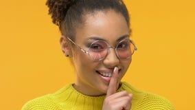 Chica joven atractiva que muestra el gesto del silencio, sosteniendo el finger cerca de los labios, secreto almacen de video