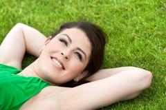 Chica joven atractiva que pone en hierba verde. Fotos de archivo