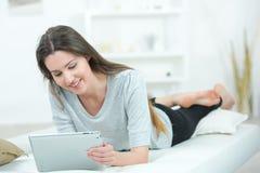 Chica joven atractiva que pone en la tableta de la tenencia de la cama Foto de archivo