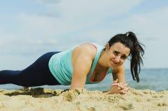 Chica joven atractiva que practica ejercicios físicos en una playa en el verano Fotografía de archivo