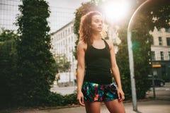 Chica joven atractiva que se coloca en la cancha de básquet Fotografía de archivo