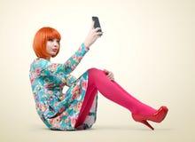 Chica joven atractiva que se sienta con un teléfono elegante imagenes de archivo