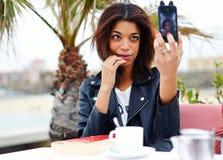 Chica joven atractiva que se sienta en sus fotografías del teléfono Imagen de archivo