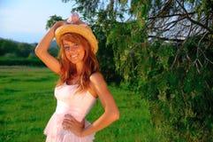Chica joven atractiva que sonríe en fondo del verde de la puesta del sol Imagen de archivo