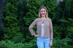 Chica joven atractiva que sonríe y que presenta a la cámara y a los soportes encendido Fotografía de archivo
