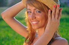 Chica joven atractiva que sonríe en fondo del verde de la puesta del sol Imagenes de archivo