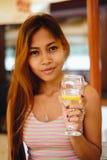 Chica joven atractiva que sostiene un vidrio y que bebe martini con el cóctel del limón Imagen de archivo