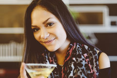 Chica joven atractiva que sostiene un vidrio y que bebe martini con el cóctel del limón Foto de archivo