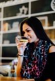 Chica joven atractiva que sostiene un vidrio y que bebe martini con el cóctel del limón Fotografía de archivo libre de regalías