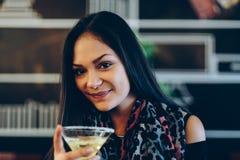 Chica joven atractiva que sostiene un vidrio y que bebe martini con el cóctel del limón Imágenes de archivo libres de regalías