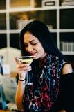 Chica joven atractiva que sostiene un vidrio y que bebe martini con el cóctel del limón Fotografía de archivo