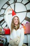 Chica joven atractiva que tira del casquillo de la Navidad Foto de archivo libre de regalías