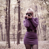 Chica joven atractiva que toma las fotos en parque del otoño Imagen de archivo