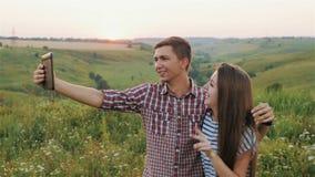 Chica joven atractiva y Guy Taking Selfie en la puesta del sol Cámara lenta almacen de metraje de vídeo
