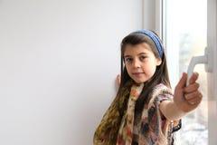 Chica joven blanca que sonríe, ventana de abertura Fotos de archivo