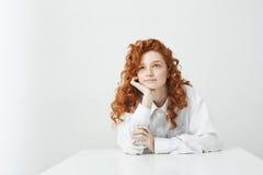 Chica joven blanda soñadora con el pelo rizado rojo que piensa soñando sentarse en la tabla sobre el fondo blanco Fotografía de archivo libre de regalías