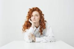 Chica joven blanda soñadora con el pelo rizado rojo que piensa soñando sentarse en la tabla sobre el fondo blanco Fotos de archivo