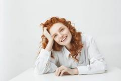 Chica joven bonita alegre con sentarse de risa sonriente del pelo astuto en la tabla sobre el fondo blanco Fotografía de archivo