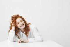 Chica joven bonita alegre con sentarse de risa sonriente del pelo astuto en la tabla sobre el fondo blanco Imagenes de archivo