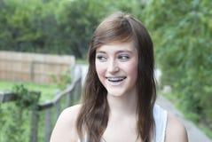 Chica joven bonita con los apoyos Smiliing y mirada al lado Fotos de archivo libres de regalías