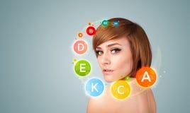 Chica joven bonita con los iconos y los símbolos coloridos de la vitamina Imagenes de archivo