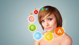 Chica joven bonita con los iconos y los símbolos coloridos de la vitamina Fotos de archivo