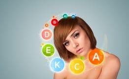Chica joven bonita con los iconos y los símbolos coloridos de la vitamina Imágenes de archivo libres de regalías