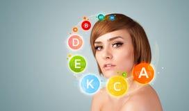 Chica joven bonita con los iconos y los símbolos coloridos de la vitamina Foto de archivo