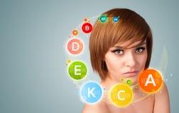 Chica joven bonita con los iconos y los símbolos coloridos de la vitamina Imagen de archivo