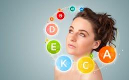 Chica joven bonita con los iconos y los símbolos coloridos de la vitamina Fotos de archivo libres de regalías