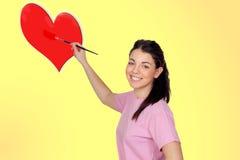 Chica joven bonita con un cepillo que pinta un corazón rojo Fotos de archivo libres de regalías