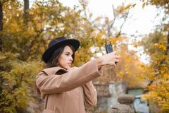 Chica joven bonita con un sombrero negro que camina en el parque Fotos de archivo libres de regalías