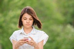 Chica joven bonita del retrato con el móvil Fotos de archivo