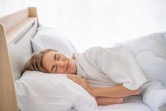 Chica joven bonita del retrato en cama en el apartamento moderno por la ma?ana Ella mantiene ojos cerrados y parece satisfecha imagenes de archivo