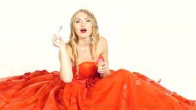 Chica joven bonita en el vestido rojo magnífico, sentándose almacen de video