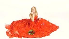Chica joven bonita en el vestido rojo magnífico, sentándose metrajes