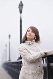 Chica joven bonita en la capa blanca en un puente Fotografía de archivo