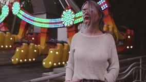 Chica joven bonita en los vidrios que presentan cerca de la atracción del oscilación en parque del amusment almacen de video