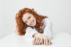 Chica joven bonita feliz con el pelo astuto que sonríe mirando la cámara que se sienta en la tabla sobre el fondo blanco Imagen de archivo