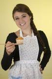 Chica joven bonita feliz que lleva cocinando el delantal Fotografía de archivo
