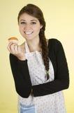 Chica joven bonita feliz que lleva cocinando el delantal Imagenes de archivo