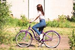 Chica joven bonita feliz que monta en bicicleta en parque del verano Feliz relaje el tiempo en ciudad Mujer hermosa, día soleado fotografía de archivo