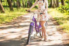 Chica joven bonita feliz que monta en bicicleta en parque del verano Feliz relaje el tiempo en ciudad Mujer hermosa, día soleado foto de archivo
