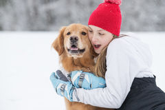 Chica joven bonita que abraza su perro del golden retriever en la nieve Imágenes de archivo libres de regalías