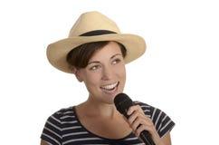 Chica joven bonita que canta con el micrófono y el sombrero Imagen de archivo libre de regalías