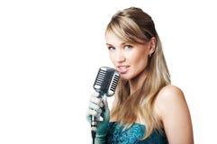 Chica joven bonita que canta en el micrófono retro Foto de archivo