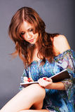 Chica joven bonita que escribió en un cuaderno fotografía de archivo libre de regalías