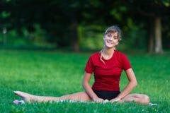 Chica joven bonita que hace ejercicios partidos Imagenes de archivo