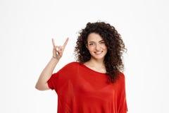 Chica joven bonita que hace gesto de la roca Imagen de archivo